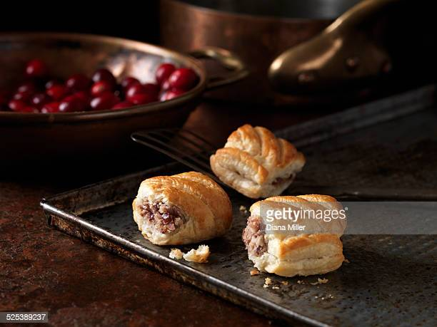 Christmas snack with pork & cranberry sausage rolls on roasting tray