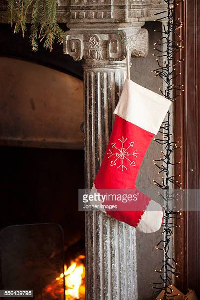 christmas sock hanging from mantelpiece - calza della befana foto e immagini stock