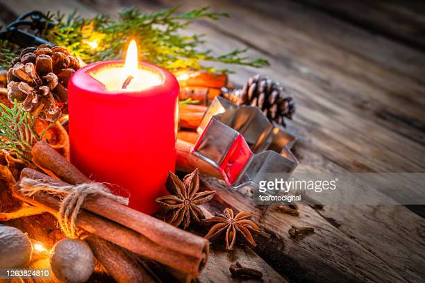 christmas spices and christmas candle on rustic wooden table. copy space - christmas decore candle stock pictures, royalty-free photos & images