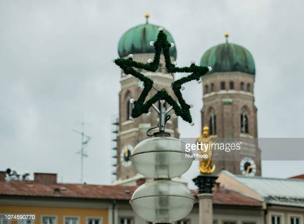 A christmas star in front of the two towers of the Cathedral of Our Dear Lady The most important christmas market of Munich at Marienplatz was full...