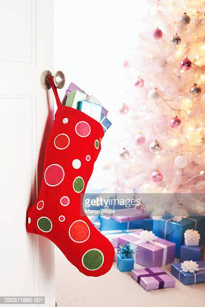 Christmas stocking filled with gifts hanging on door handle