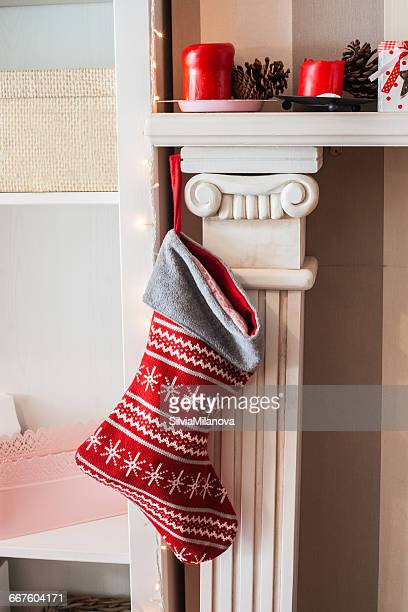 christmas stocking hanging on fireplace - calza della befana foto e immagini stock
