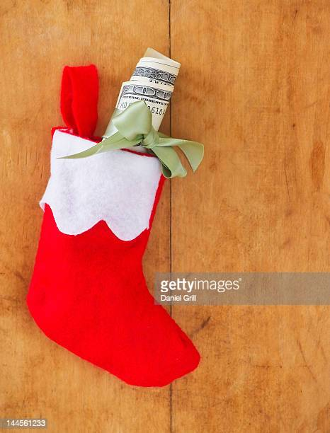 christmas stocking with roll of banknotes - christmas cash stock pictures, royalty-free photos & images