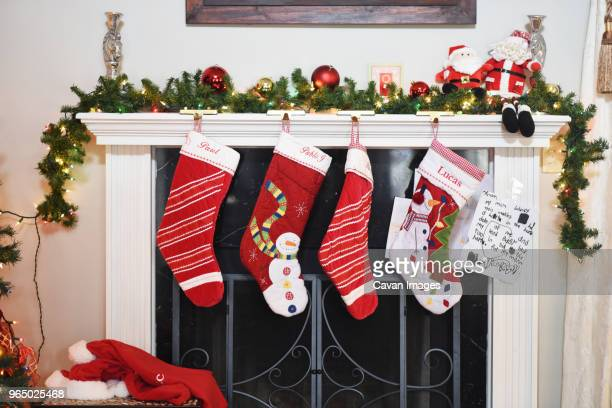 christmas stockings hanging by fireplace at home - calza della befana foto e immagini stock