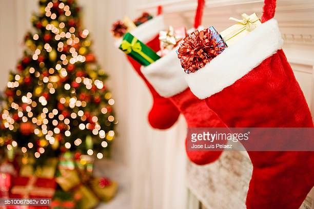 Christmas stockings hanging, Christmas tree in background, close-up