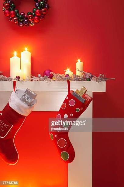 christmas stockings hanging from the fireplace - christmas decore candle stock pictures, royalty-free photos & images