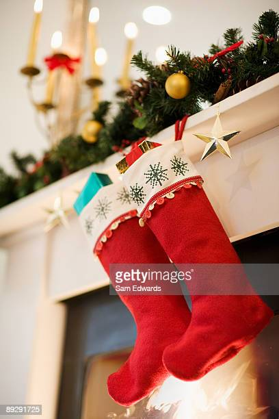 christmas stockings hanging on fireplace mantel - calza della befana foto e immagini stock