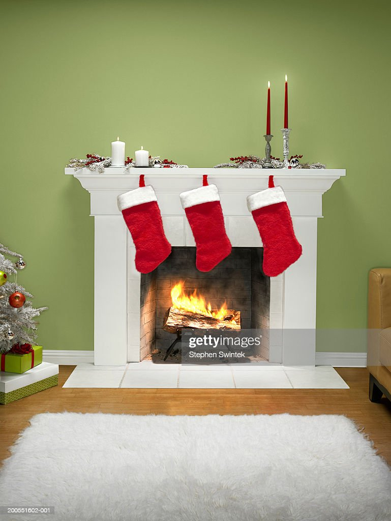 Christmas stockings hanging over fireplace : Stock Photo