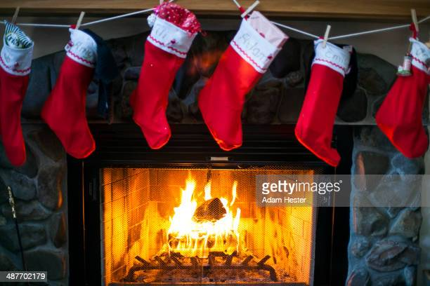 christmas stockings hanging over fireplace - calza della befana foto e immagini stock