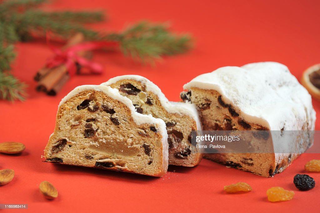 Christmas stollen on a red background. The frame space is occupied by slices of cake, cinnamon sticks, raisins and almond nuts. Close-up. : Stock Photo