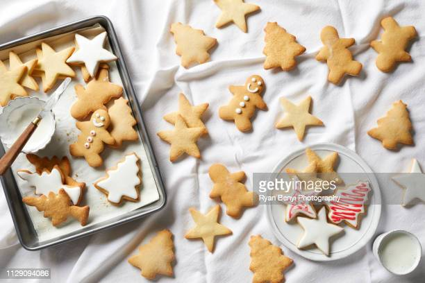 christmas sugar cookies being iced, overhead view - christmas cookies stock pictures, royalty-free photos & images