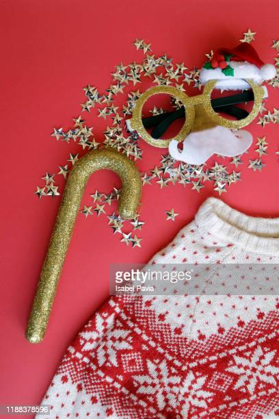 christmas sweater and details on red background - 醜さ ストックフォトと画像