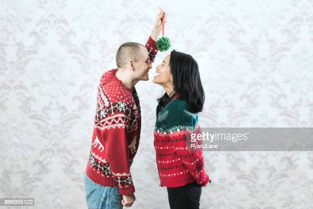 christmas sweater couple kiss under mistletoe - mistletoe stock photos and pictures