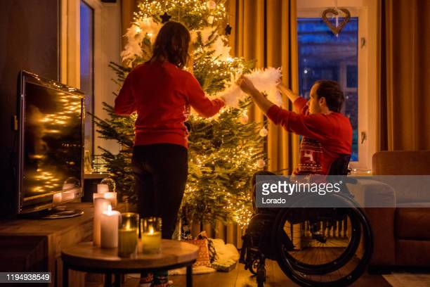 christmas sweaters for disabled couple in xmas home - ugly christmas sweater party stock pictures, royalty-free photos & images