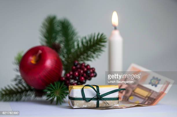 Christmas Symbol photo on the subject of Christmas money small or large gifts etc The photo shows Christmas decoration with candle a gift package and...