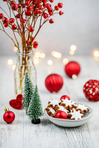 Christmas table decoration with red Christmas tree balls and a vase with Christmas branches and red berries. String of lights in the background.