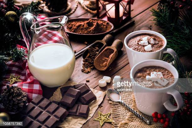 christmas table setup with homemade two chocolate mug with marshmallows and candlelight lamp - hot chocolate stock pictures, royalty-free photos & images