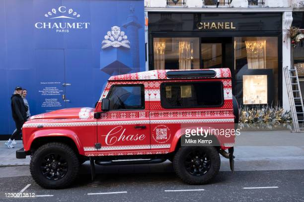 Christmas themed red liveried Jeep 4x4 SUV on Bond Street exclusive shopping district on 1st December 2020 in London, United Kingdom. Bond Street is...