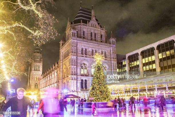 Christmas time decoration in London. Evening outside of the Natural History Museum of London with Christmas decoration, a carousel, an Ice Rink and a...