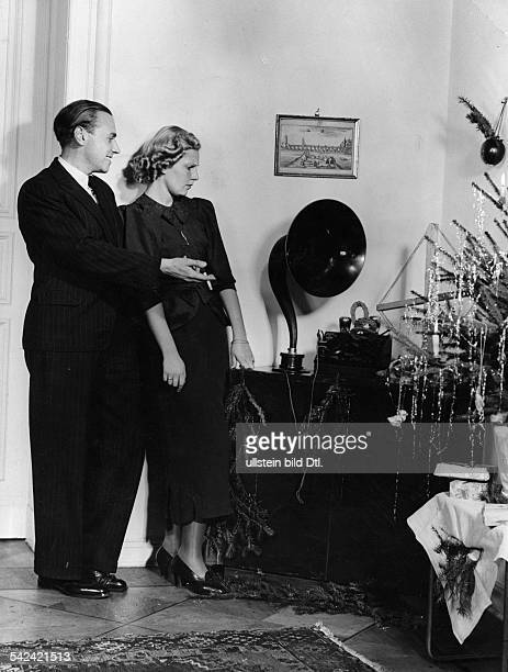 Christmas time Young woman looking with dismay at the gramophone made by her husband 1937 Photographer Peter Weller Vintage property of ullstein bild