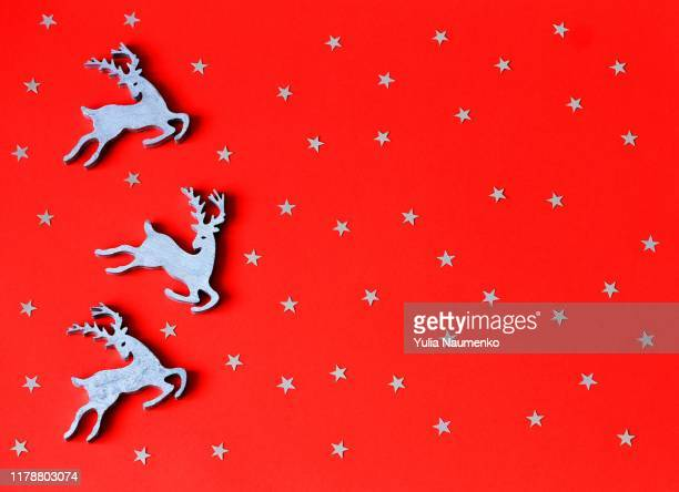 christmas toys wooden deers on red paper background with decorative stars. top view, copy space. - christmas banner stock photos and pictures