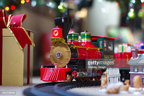 Christmas train under tree with wrapped gifts