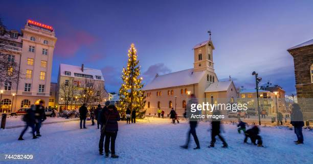 christmas tree and domkirkjan church. people enjoying a winter evening in downtown, reykjavik during christmas time, iceland. - reykjavik stock pictures, royalty-free photos & images