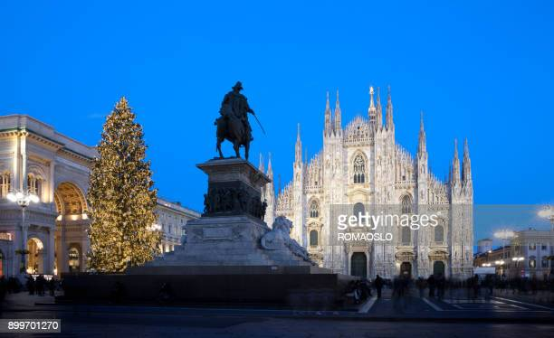 Christmas tree and monument in Milan at dusk with the cathedral facade. Milano Italy