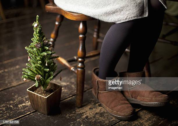 christmas tree and woman's legs wearing ugg boots - sheepskin boot stock photos and pictures