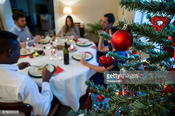 Christmas tree bauble and friends having Christmas dinner