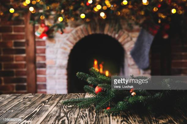 christmas tree branch on a wooden table against the background of a fireplace, place for text, christmas concept, christmas toys and blurry lights - holiday stock pictures, royalty-free photos & images