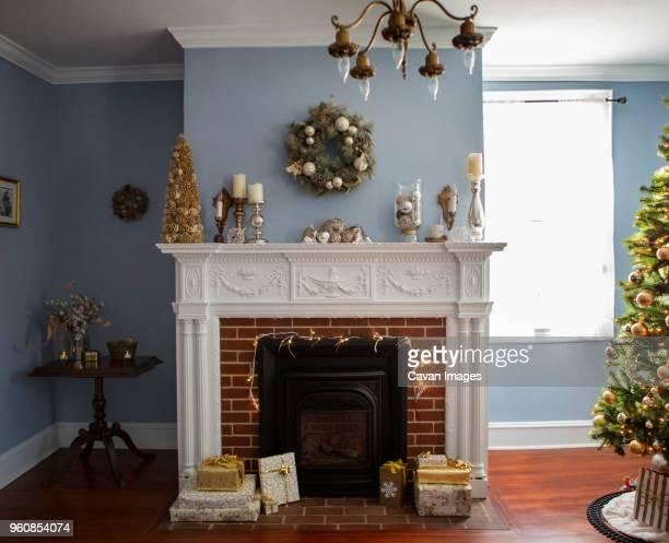 christmas tree by fireplace with decoration at home - consolo de lareira - fotografias e filmes do acervo