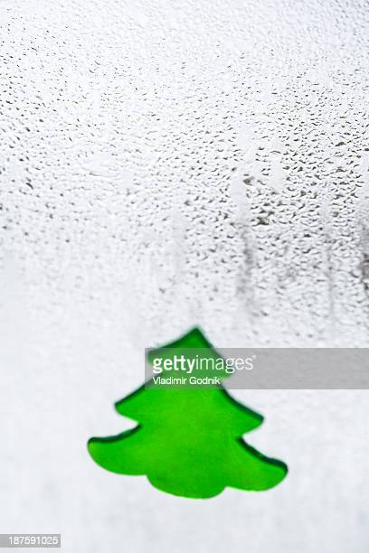A Christmas tree decal on a window with condensation on it, close-up