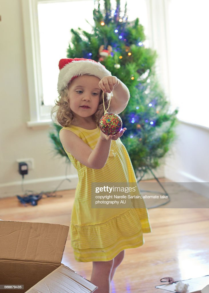 Christmas tree decorating by young girl : Stock Photo