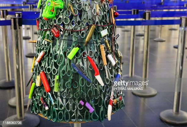 """Christmas tree"""" deftly made and decorated using items that passengers had to leave behind during screening is on display at the airport departures'..."""