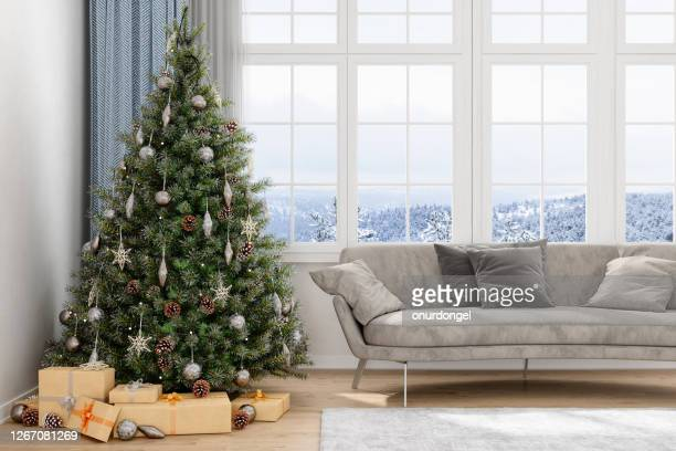 christmas tree, gifts and sofa with a view of snow - christmas trees stock pictures, royalty-free photos & images