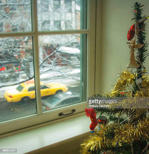 Christmas tree in a Greenwich Village apartment, with a view on a snowy NY street and a yellow taxi passing by.