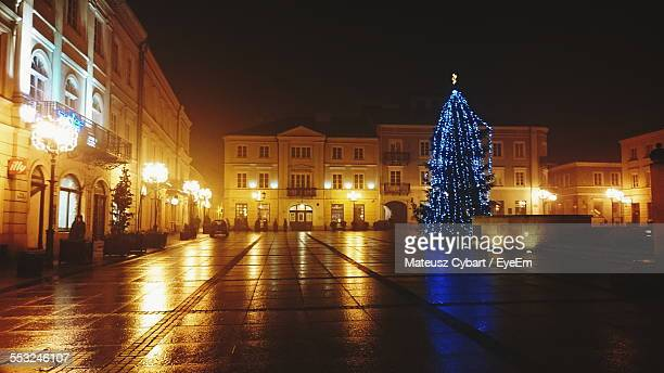 Christmas Tree In Front Of Illuminated Buildings Against Clear Sky