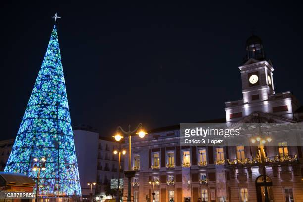 christmas tree in la puerta del sol in madrid, spain, with real casa de correos on the background - puerta del sol fotografías e imágenes de stock
