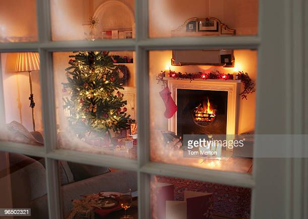 christmas tree in living room behind window - window stock pictures, royalty-free photos & images