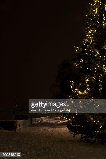 A Christmas Tree Lights A Snowy Riverside Walkway Stock Photo ...