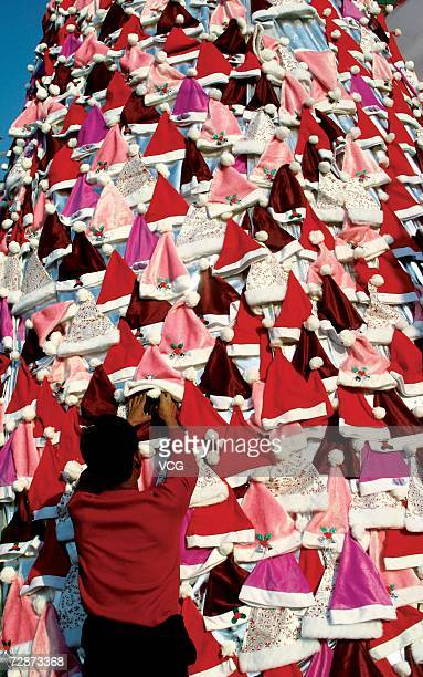 A Christmas tree made of a lot of Santa Claus hats stands decorated for upcoming Christmas outside of the shopping center on December 22 2006 in...