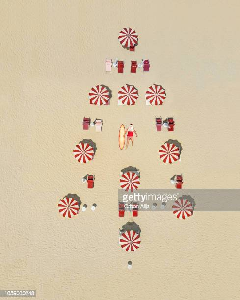christmas tree made of sun umbrellas in sand, santa claus is sunbathing. - beach christmas stock pictures, royalty-free photos & images