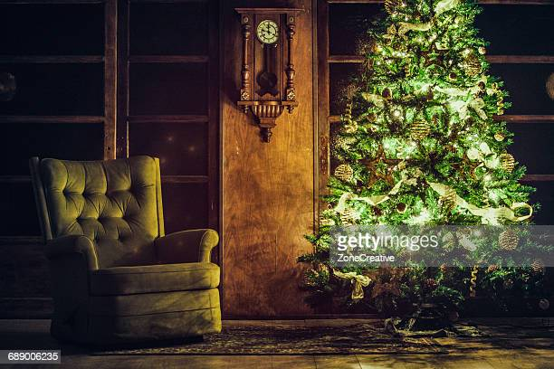 Christmas tree near green armchair in a old house