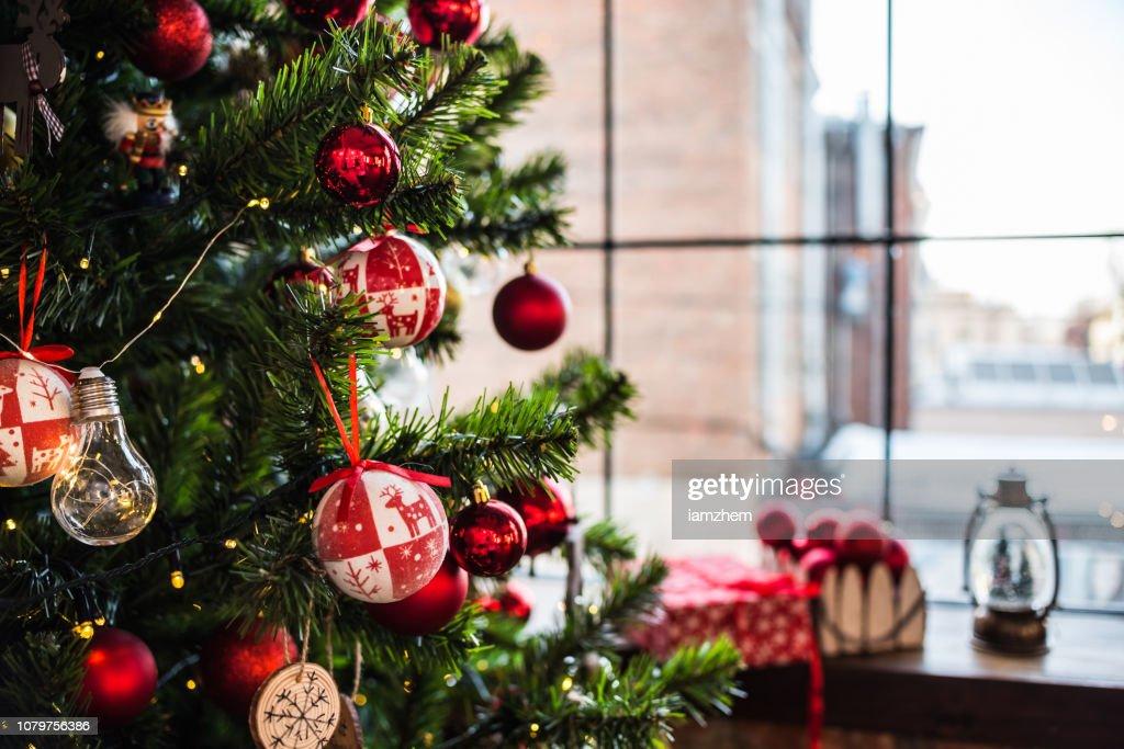 Kerstboom in de buurt van het venster op de vensterbank gave en ballonnen. Nieuwjaar 2019. : Stockfoto
