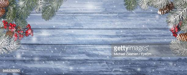 christmas tree on wooden table against wall - christmas wallpaper stock pictures, royalty-free photos & images