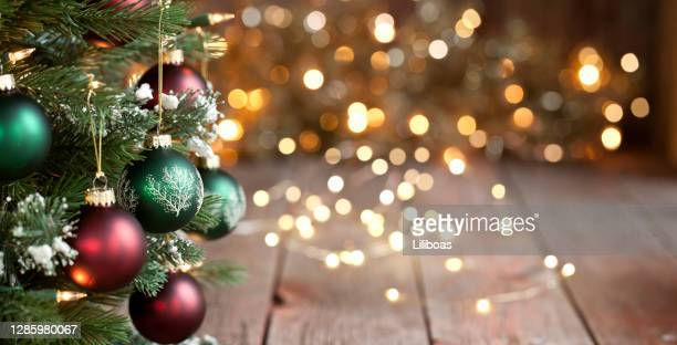 christmas tree, red and green ornaments against a defocused lights background - christmas stock pictures, royalty-free photos & images