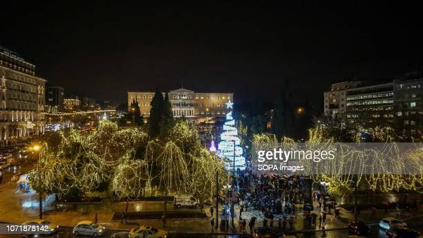 Christmas tree seen in the background at the Hellenic Parliament Building in Syntagma Square Thousands of people turned up during the switch on of...