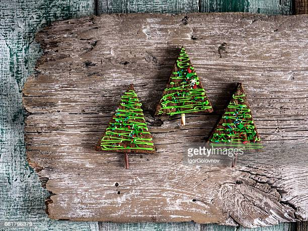 Christmas tree shaped cakes on wooden plank