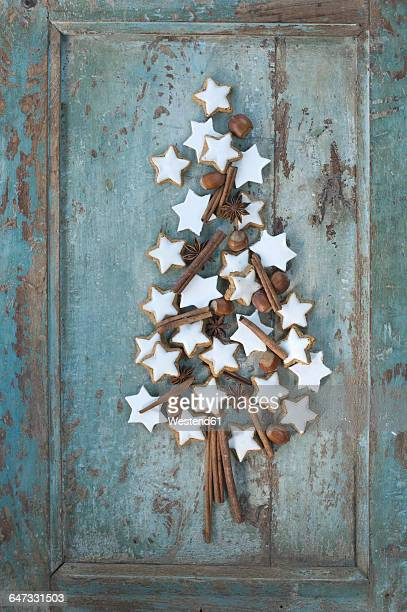 Christmas tree shaped of cinnamon stars, cinnamon sticks, star anise and hazelnuts
